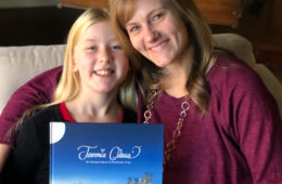 Photo of Megan Holmes and her daughter, Madeline, holding the Jammie Claus book