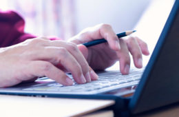 Close-up photo of hands typing on a laptop