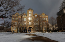 Photo taken from ground-level down a snow-covered path leading to Adelbert Hall as students walk by