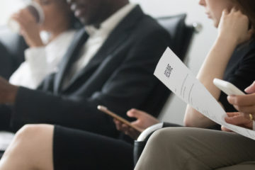 Photo of job applicants in a waiting room with one holding a resume