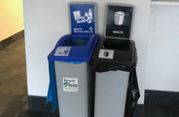 Photo of a recycling bin and trash bin standing side-by-side on campus
