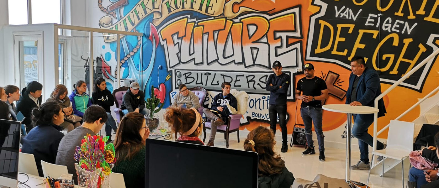 Photo of students participating in a discussion in front of a large wall mural during a study abroad course in The Netherlands