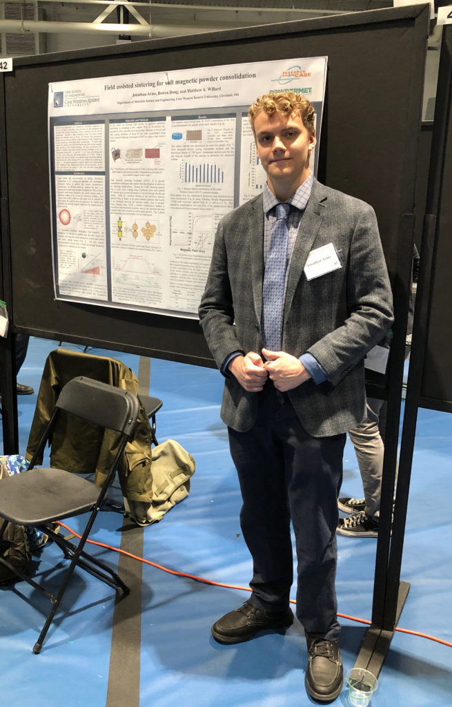 Photo of Jonathan Arms standing next to a poster presentation