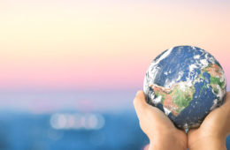 Artistic photo of a globe held in the palms of two hands with a blurred background