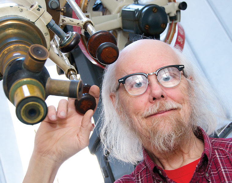 Photo of Charley Knox posing with a telescope