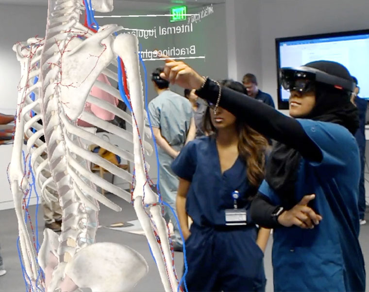 Two students wearing virtual reality visors gesturing toward an image of a skeleton