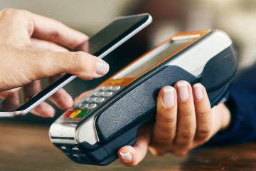 someone paying with a phone, hovering a smartphone over handheld credit card reader