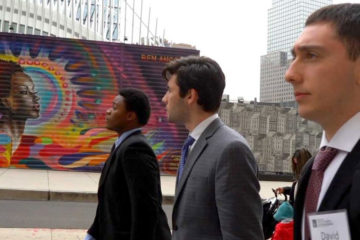 Three students walking on a street in New York City in front of a colorful mural