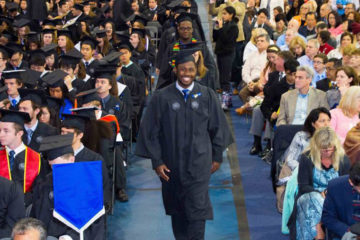 Students in graduation gowns walking through a seated crowd at a graduation ceremony