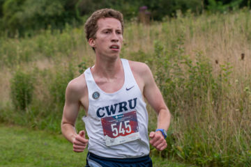 David Hall running in a cross-country meet with tall grass in the background