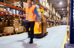 blurry image of a warehouse worker and a forklift among boxes at a warehouse