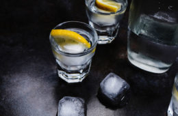 two glasses and a pitcher with clear liquid ice and lemon slices on a dark background