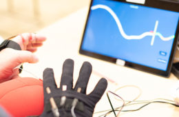 a closeup of a hand wearing a glove and the corresponding electrical signals on a computer screen