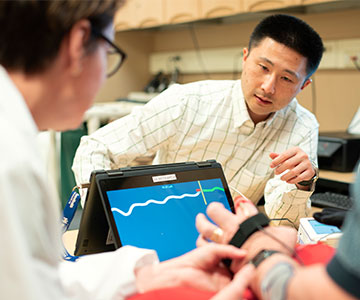 Assistant professor Michael Fu works with a patient who is wearing a band on his hand to measure muscle activity