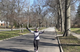 runner with arms extended running toward camera on an empty street