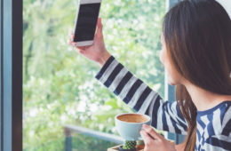 Photo of a woman taking a selfie while holding a cup of coffee
