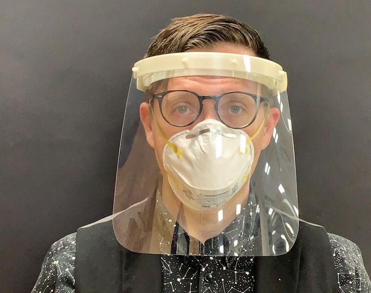 Ian Charnas demonstrating a face shield.