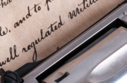 gun rests on top of a copy of the Constitution