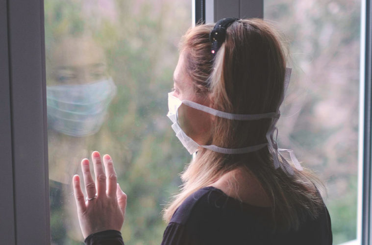 quarantined woman looks out the window