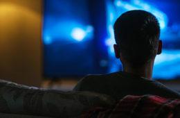 man watches television in the dark