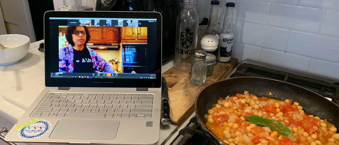Kitchen scene of a pan with food on a stovetop next to an open laptop with the image of a person in a kitchen