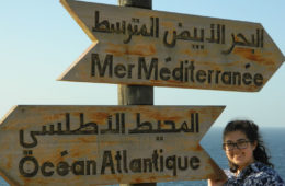 Student standing next to a sign with the words Atlantic Ocean in several languages