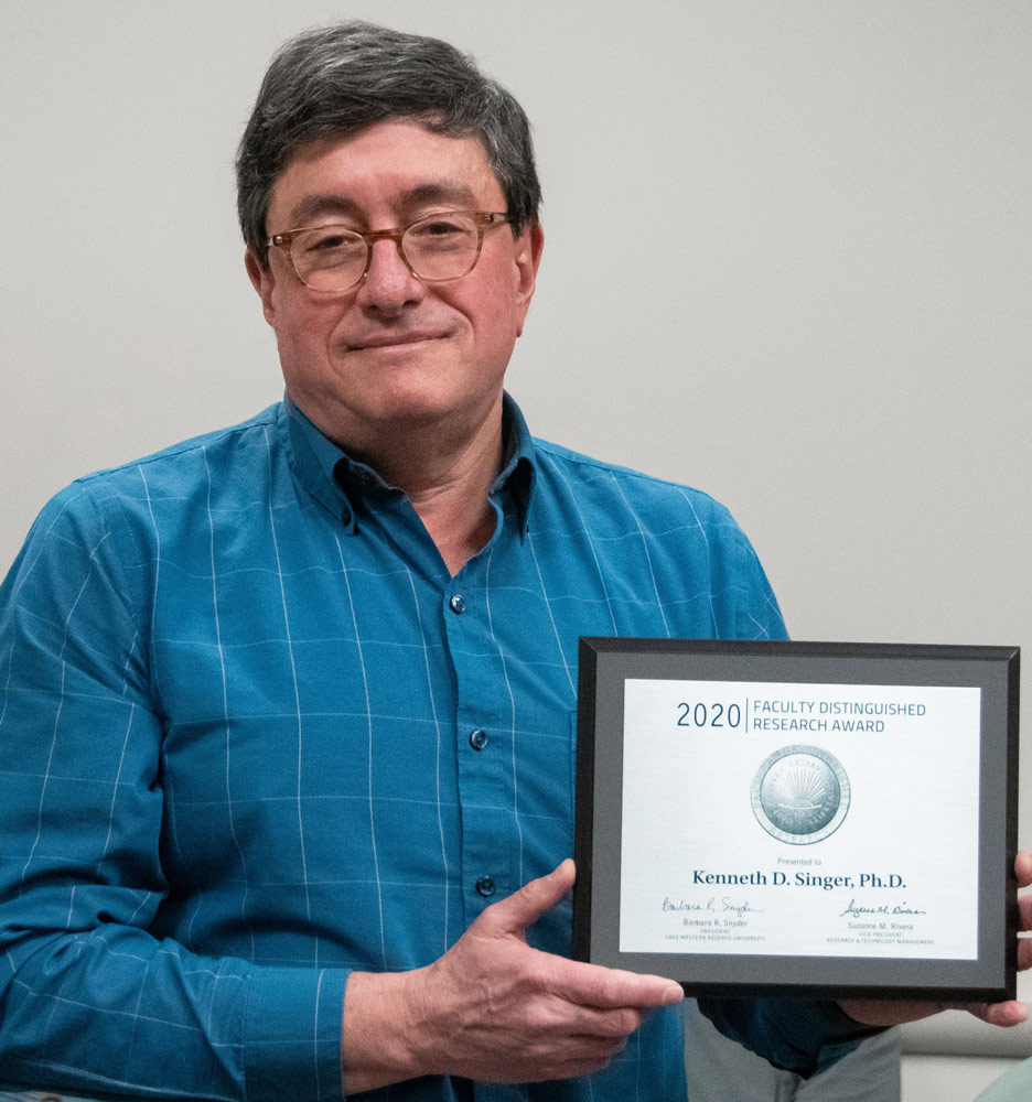 Photo of Kenneth Singer holding an award plaque