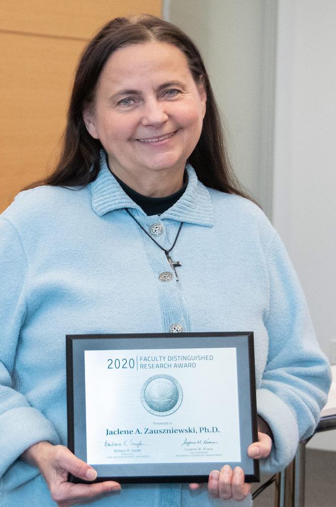 Photo of Jaclene A. Zauszniewski holding an award plaque