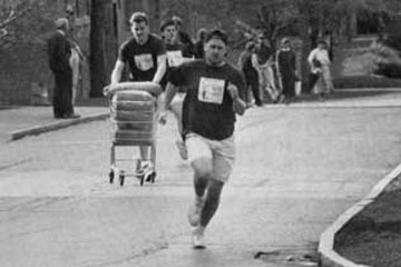 Black and white photo of students participating in a Spring Olympics event with students running, one with a shopping cart