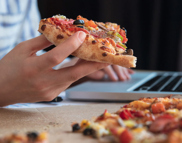 Photo of someone holding a piece of pizza while on a laptop