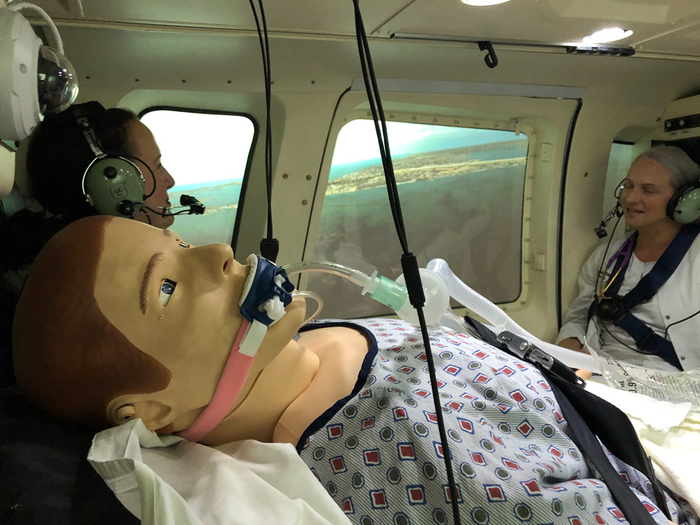 Photo of a dummy being used as a patient in a simulated emergency flight with two nurses