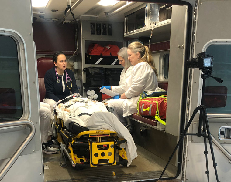 Photo of three nurses in the back of a simulated ambulance while a camera records