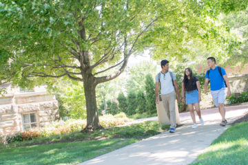 Photo of three students walking across Case Quad