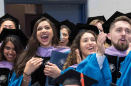 Photo of doctorate graduates cheering during a commencement celebration