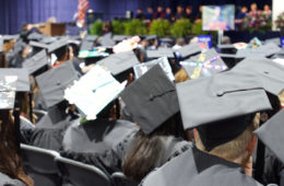 Photo from behind of graduates' caps during commencement ceremony