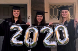 Photo of three graduates wearing caps and gowns and holding out balloons that say 2020
