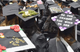"Photo from behind of decorated grad caps during 2019 commencement, including one that says ""be the change you wish to see"""