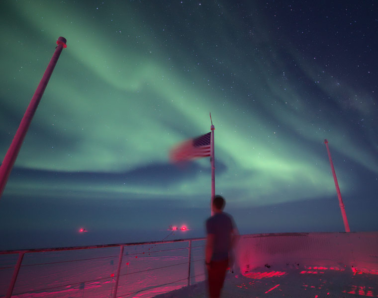Photo of Allen Foster standing on the station deck looking out at the auroras overhead in the night sky