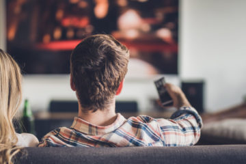 Photo from behind of a woman and man sitting on a couch watching TV as the man points remote