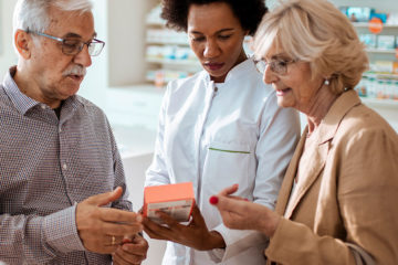Photo of an elderly couple looking at a prescription box with a doctor