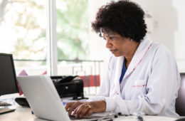 Photo of a doctor in her office typing on a laptop