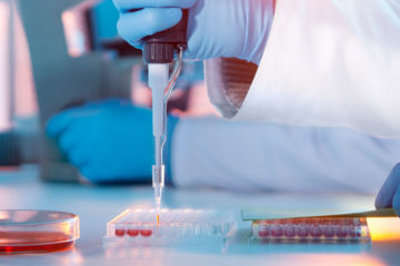 Photo of a lab setting with a technician's gloved hand using a pipette