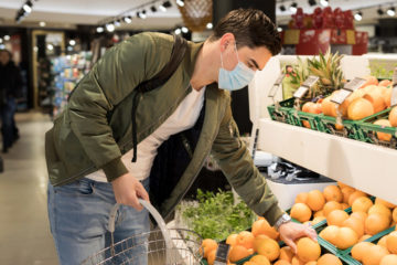 Photo of a man wearing a mask in a supermarket putting produce in his shopping basket