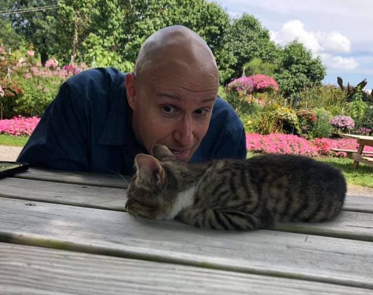 Photo of Rob Igo with a cat laying on a picnic table