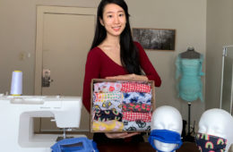Clare Shin holding a box of face masks next to a sewing machine