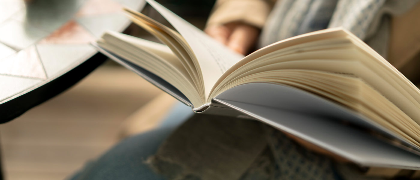 Close up photo of a person holding a book open to read it