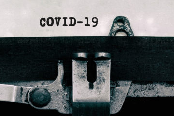 Black and white photo of a typewriter with paper saying COVID-19