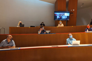 Photo of faculty and staff sitting with space between them in a Peter B. Lewis Building lecture hall
