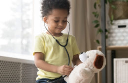 Photo of a young boy playing doctor by placing a stethoscope on stuffed dog