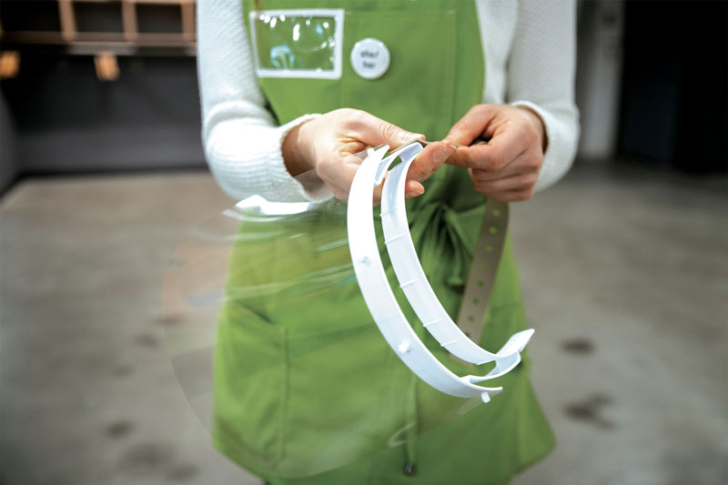 A person wearing a green apron holds face shields
